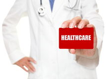 Weiblicher Doktor, der GESUNDHEITSWESEN-Karte anhält stockbild