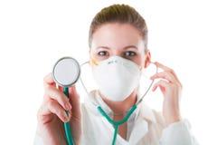 Weiblicher Doktor in der Maske mit spitzem Stethoskop Stockfoto