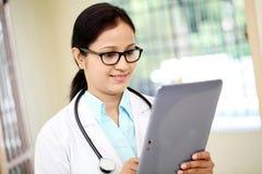 Weiblicher Doktor, der Tablettecomputer verwendet Stockfotos