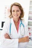 Weiblicher Doktor des glücklichen mittleren Alters in Sprechzimmer Stockfotos