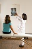 Weiblicher Doktor Showing ein Röntgenstrahl zu einem kleinen Mädchen Stockbild