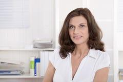 Weiblicher Doktor von mittlerem Alter im Porträt, das am Schreibtisch sitzt lizenzfreie stockbilder