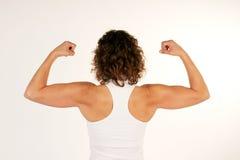 Weiblicher Eignungausbilder, der Armmuskeln biegt Stockfoto
