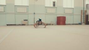 Weiblicher Eignungsathlet, in der Turnhalle, führt einen akrobatischen Satz durch stock video