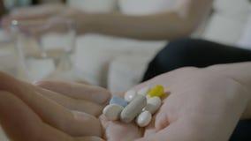 Weiblicher Eignungslehrer, der viele Ergänzungen und Pillen nimmt, um in Form zu bleiben nährt - stock video