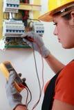 Weiblicher Elektriker, der fusebox überprüft stockbild