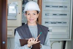 Weiblicher Elektriker des Porträts mit Klemmbrett am fusebox stockfotografie