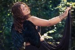 Weiblicher Engel mit schwarzen Flügeln auf einem schwarzen Hintergrund Lizenzfreies Stockbild