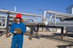 Weiblicher Erdgasfeldbediener prüft Verdichtersite Stockfotografie