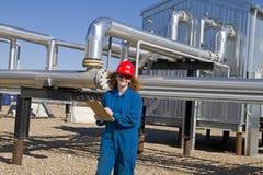 Weiblicher Erdgasfeldbediener prüft Verdichtersite Stockfotos