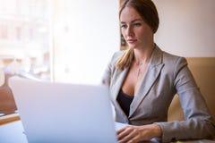 Weiblicher erfahrener Werbetexter, der fördernden Text für die Werbung des Standorts unter Verwendung des modernen netbook schrei lizenzfreie stockfotografie
