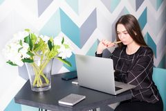 Weiblicher ernster Marketingspezialist, der an Netzbuch während des Arbeitsbruches arbeitet Online erlernend Lizenzfreies Stockbild