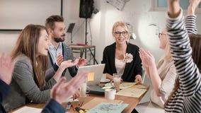 Weiblicher Führer berichtete über gute Nachrichten, jeder ist glücklich, hoch--fiving Geschäftsteam in einem modernen Startbüro Stockbild
