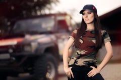 Weiblicher Fahrer in der Armee-Ausstattung nahe bei einem weg Straßen-Auto Stockbild