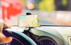 Weiblicher Fahrer, der im intelligenten Mobiltelefon des Autogebrauches mit Karte gps-Navigationsanwendung sitzt Stockfoto