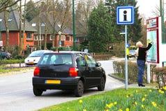 Weiblicher Fahrer ist verloren und ein Straßeninformationsbrett, die Niederlande betrachtet Stockfoto