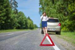 Weiblicher Fahrer nach Zusammenbruch nennend zu einer Autounterstützung stockbild