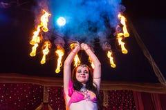 Weiblicher Feuer-Tänzer Holding Flaming Apparatus Stockfoto