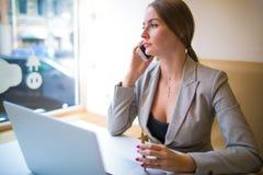 Weiblicher Finanzier, der Smartphonegespräch während des Arbeitsbruches hat stockfoto