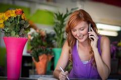 Weiblicher Florist, der Bestellung am Handy entgegennimmt stockbilder
