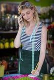 Weiblicher Florist, der Bestellung am Handy entgegennimmt stockfoto