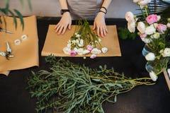 Weiblicher Florist, der Blumenblumenstrauß auf schwarzer Tabelle entwirft und herstellt Lizenzfreies Stockfoto