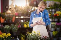 Weiblicher Florist, der eine Bestellung am Handy entgegennimmt stockbild
