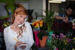 Weiblicher Florist, der eine Bestellung am Telefon entgegennimmt lizenzfreie stockfotografie