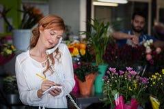 Weiblicher Florist, der eine Bestellung am Telefon entgegennimmt lizenzfreie stockbilder