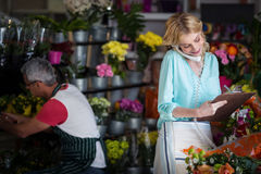 Weiblicher Florist, der eine Bestellung am Telefon entgegennimmt stockfoto