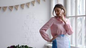Weiblicher Florist, der am Handy spricht und Blumen kontrolliert stockfotografie