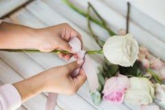 Weiblicher Florist, der schönen Blumenstrauß am Blumenladen macht Stockbilder