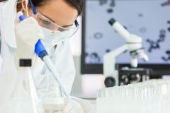 Weiblicher Forschungs-Wissenschaftler With Pipette u. Flasche im Labor Lizenzfreie Stockfotografie