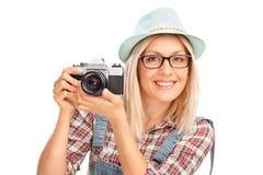 Weiblicher Fotograf, der eine Kamera anhält Lizenzfreie Stockfotos