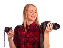 Weiblicher Fotograf, der zwischen zwei Kameras - lokalisiert auf w wählt Stockfotografie