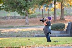 Weiblicher Fotograf mit dem purpurroten Haar im Park lizenzfreie stockbilder