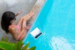 Weiblicher Freiberufler sitzt durch das Pool und arbeitet an einem Laptop und lässt den Laptop in das Wasser fallen Beschäftigt w lizenzfreies stockfoto