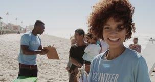 Weiblicher Freiwilliger, der Kamera auf dem Strand 4k betrachtet stock video