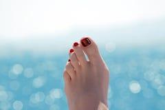 Weiblicher Fuß über blauem Ozean am sonnigen Tag Stockfotos