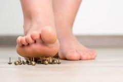 Weiblicher Fuß über Druckbolzen Stockfotografie