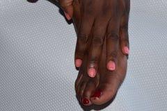 Weiblicher Fuß mit einer manikürten Hand Stockbild