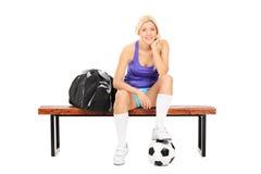 Weiblicher Fußballspieler, der auf einer Bank sitzt Lizenzfreie Stockfotos