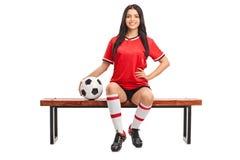Weiblicher Fußballspieler, der auf einer Bank sitzt Lizenzfreie Stockbilder