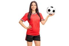 Weiblicher Fußballspieler im roten Trikot, das einen Ball hält Lizenzfreie Stockfotos