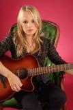 Weiblicher Gitarrist, der auf ledernem Stuhl sitzt Lizenzfreies Stockfoto
