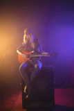 Weiblicher Gitarrist, der auf Sprecher bei der Ausführung im Nachtklub sitzt Lizenzfreies Stockfoto