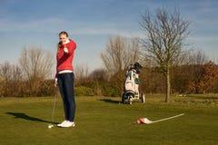 Weiblicher Golfspieler, der Daumen aufgibt Stockbild