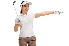 Weiblicher Golfspieler, der einen Golfclub hält und nach rechts zeigt Lizenzfreies Stockfoto