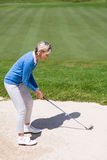 Weiblicher Golfspieler, der einen Schuss nimmt Lizenzfreie Stockfotografie