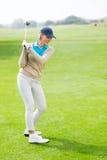 Weiblicher Golfspieler, der einen Schuss nimmt Lizenzfreies Stockbild